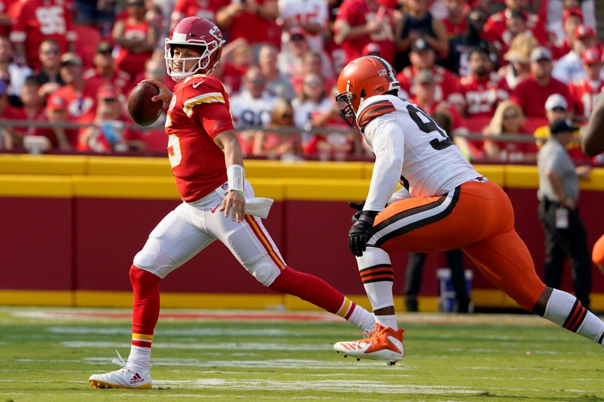Kansas City Chiefs quarterback Patrick Mahomes, left, scrambles away from Cleveland Browns defe ...