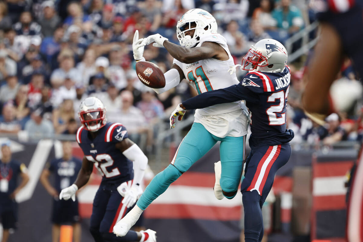 New England Patriots defensive back J.C. Jackson, right, breaks up a pass to Miami Dolphins wid ...