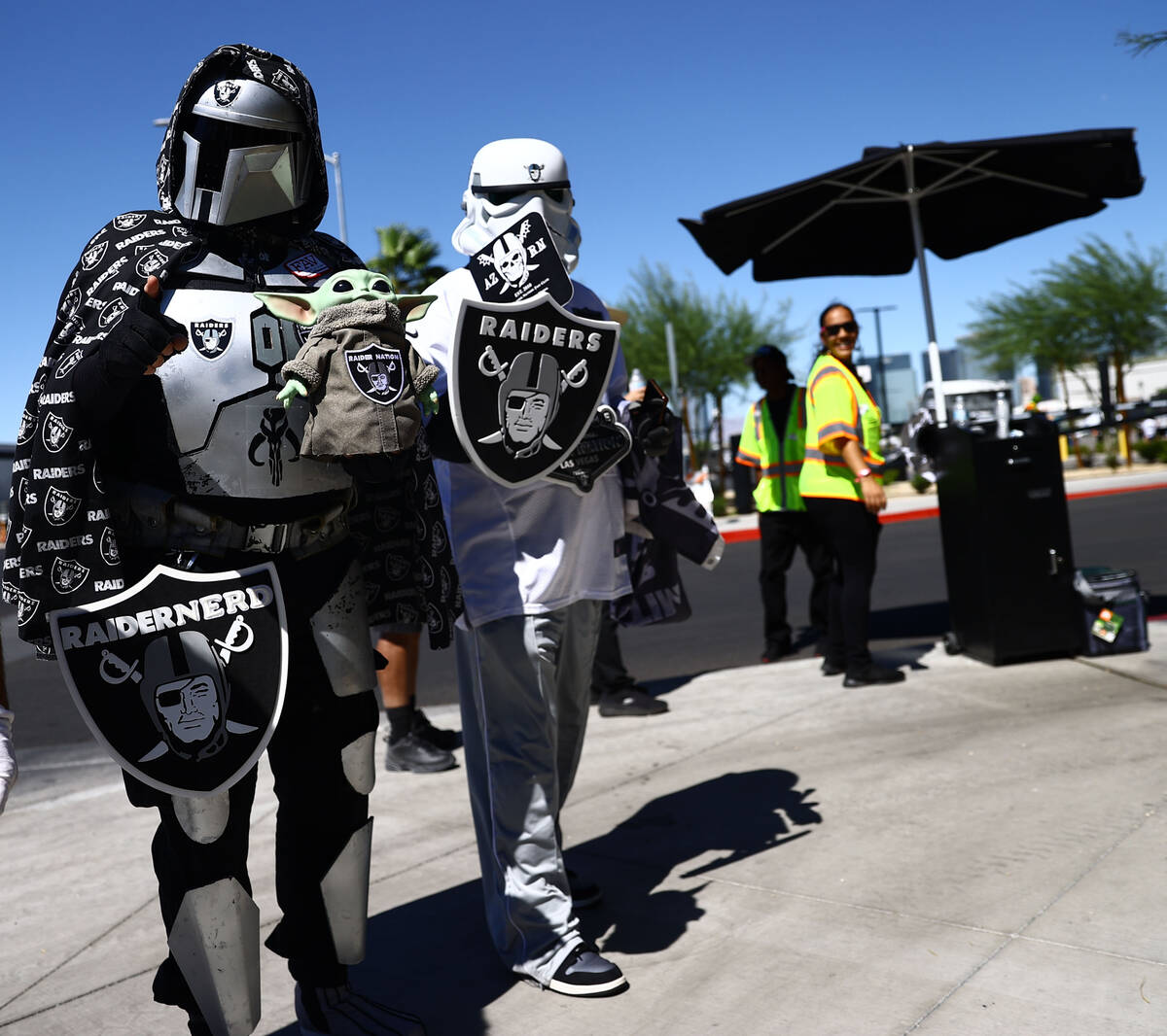 Fans wearing costumes walk around before an NFL football game between the Raiders and the Balti ...