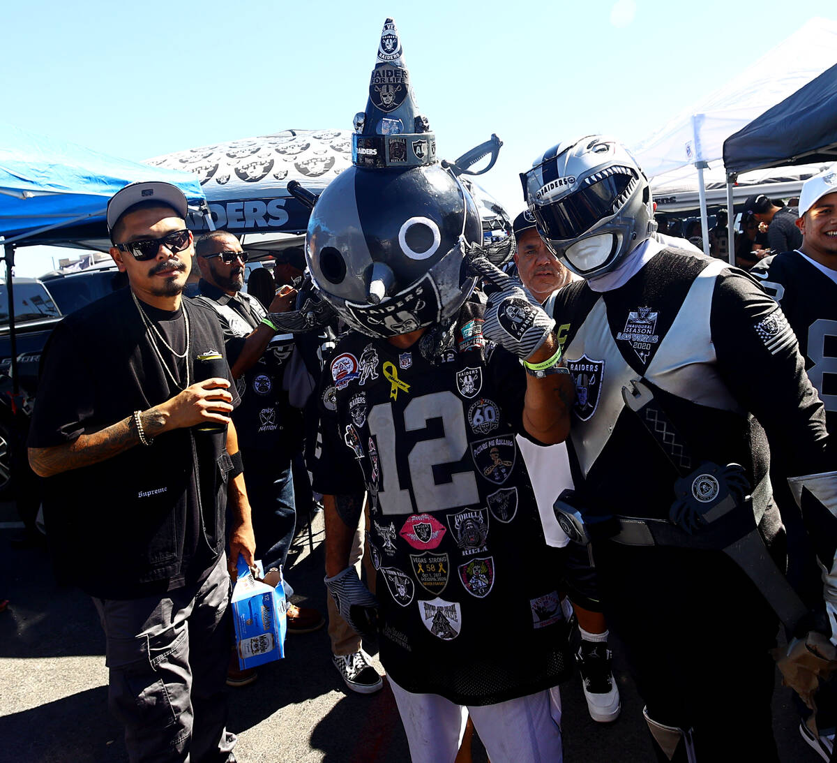 Fans spend time tailgating before an NFL football game between the Raiders and the Baltimore Ra ...