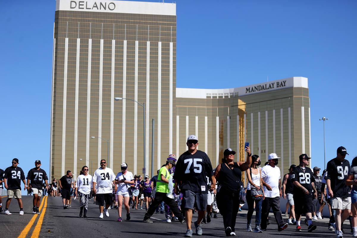 Fans cross the Hacienda Avenue bridge toward Allegiant Stadium for a game between the Raiders a ...
