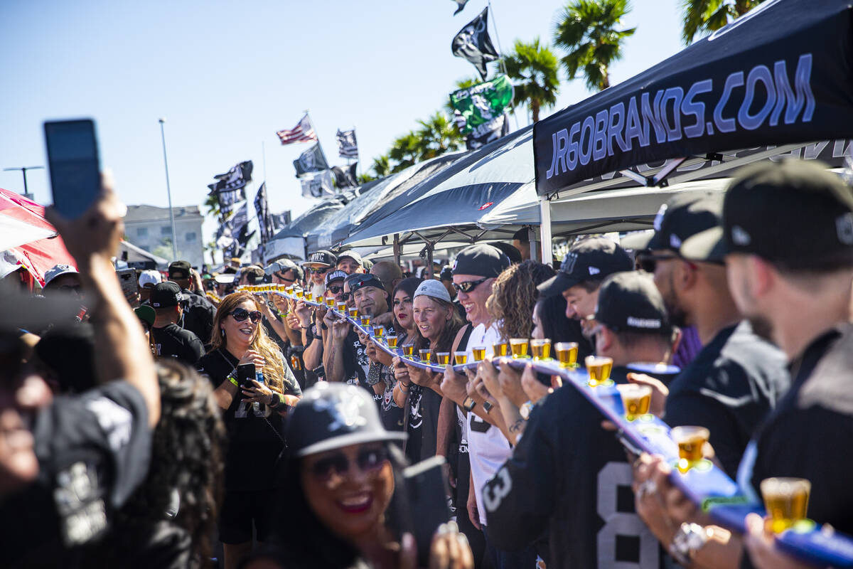 Over 100 football fans prepare to take shots while tailgating before an NFL game between the Ra ...