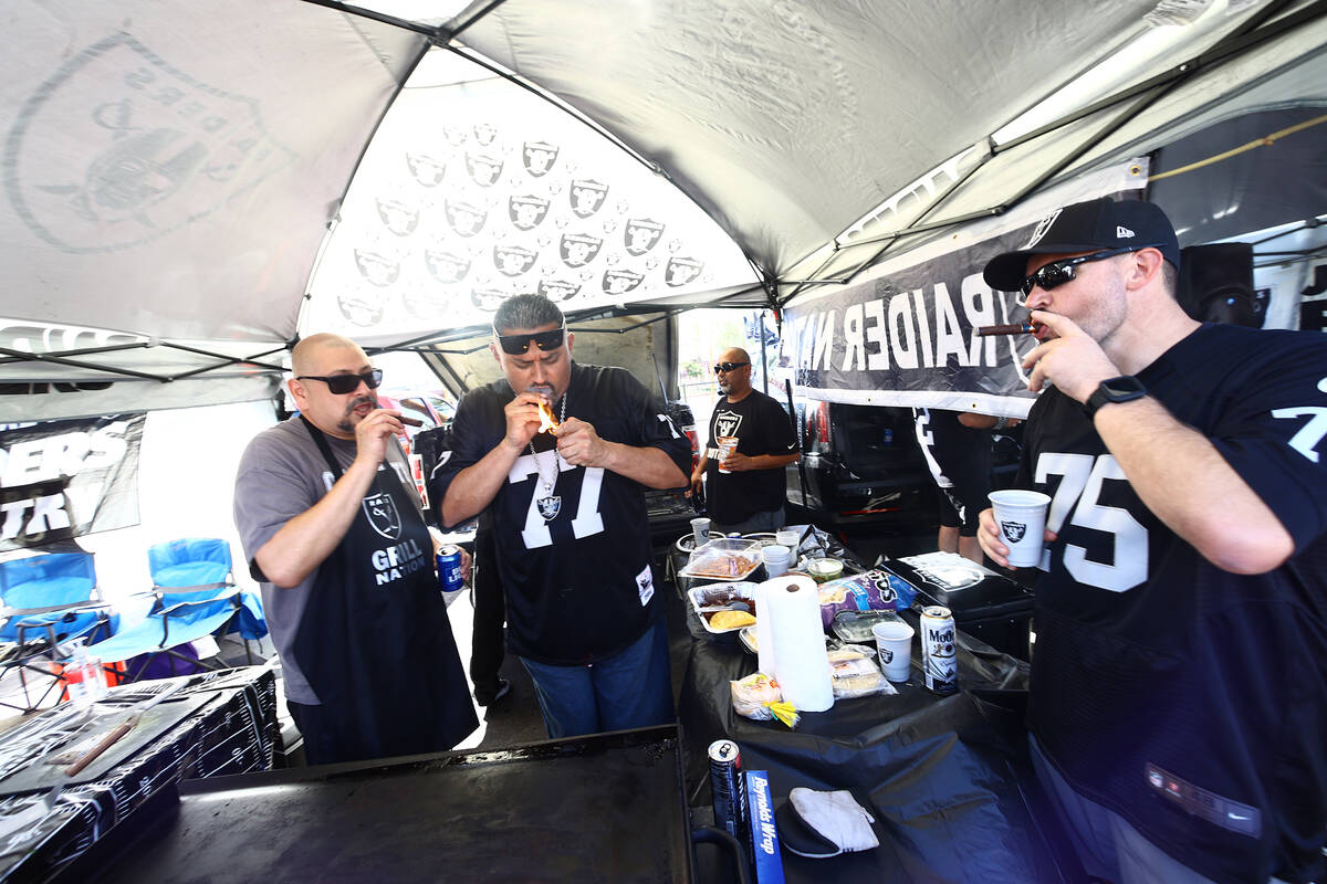 Raiders fans light cigars ahead of the team's game against the Baltimore Ravens on Monday, Sept ...