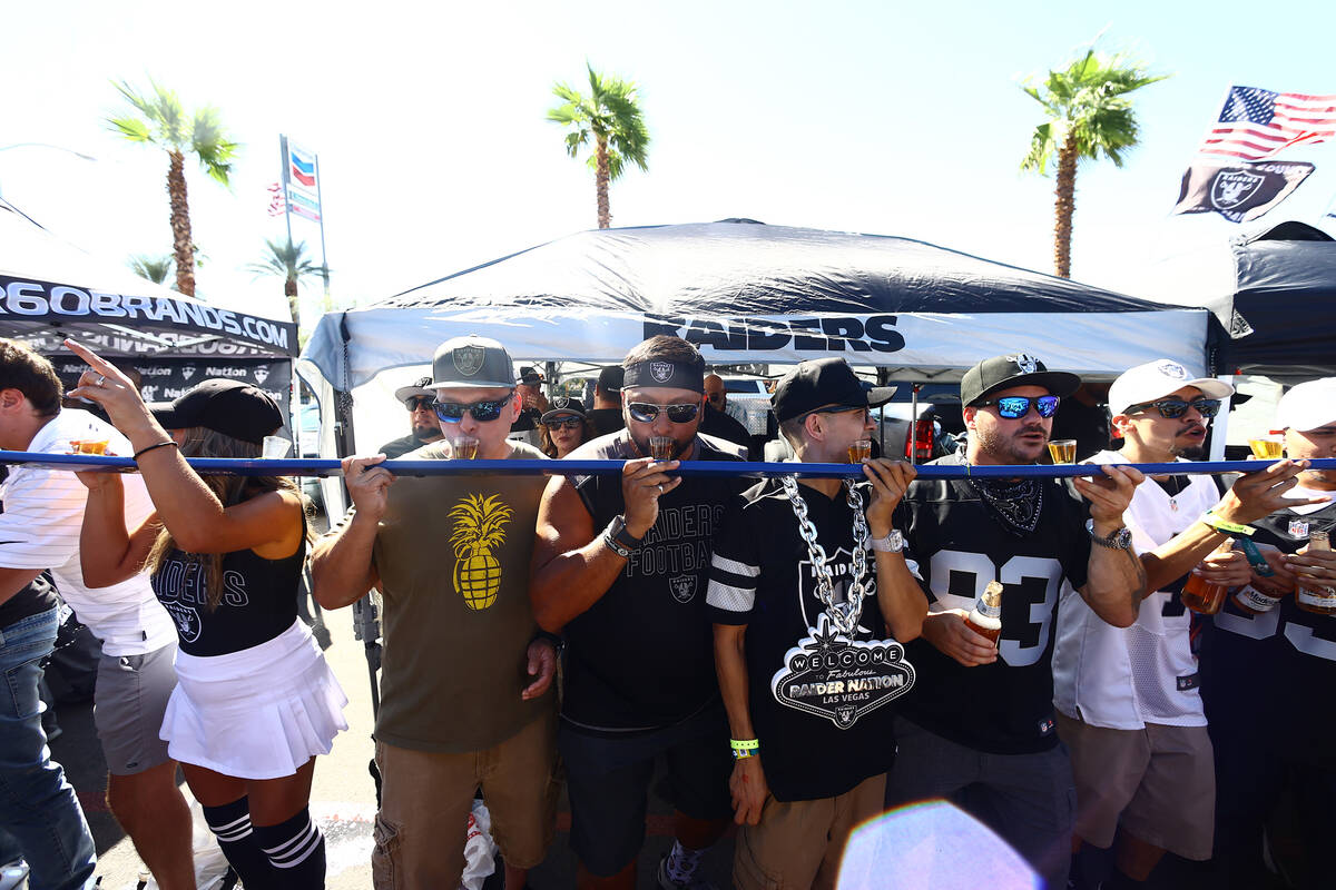 Raiders fans tailgate outside of Allegiant Stadium ahead of the team's game against the Baltimo ...