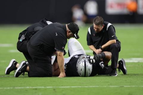 Las Vegas Raiders offensive guard Denzelle Good (71) lies on the field after getting injured ag ...