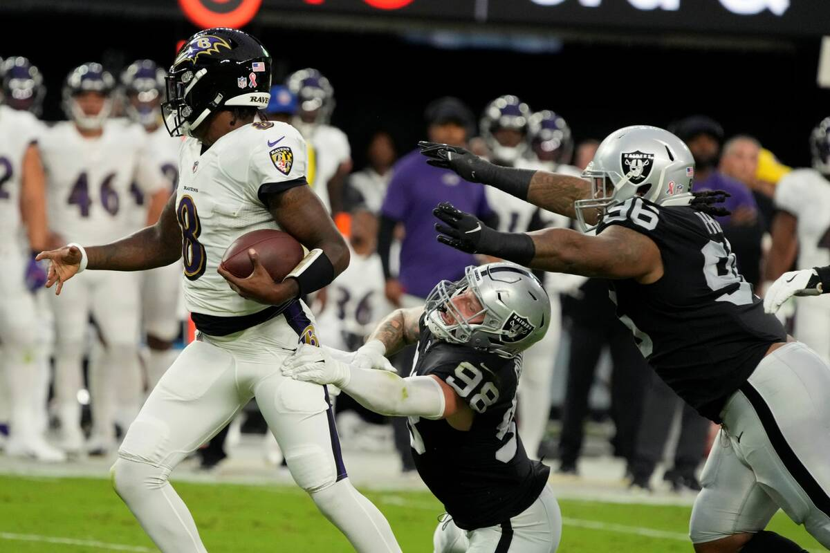 Las Vegas Raiders defensive end Maxx Crosby (98) grabs Baltimore Ravens quarterback Lamar Jacks ...