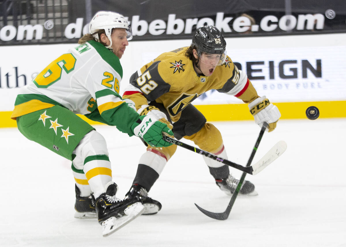 Wild center Gerald Mayhew (26) and Golden Knights defenseman Dylan Coghlan (52) compete for the ...