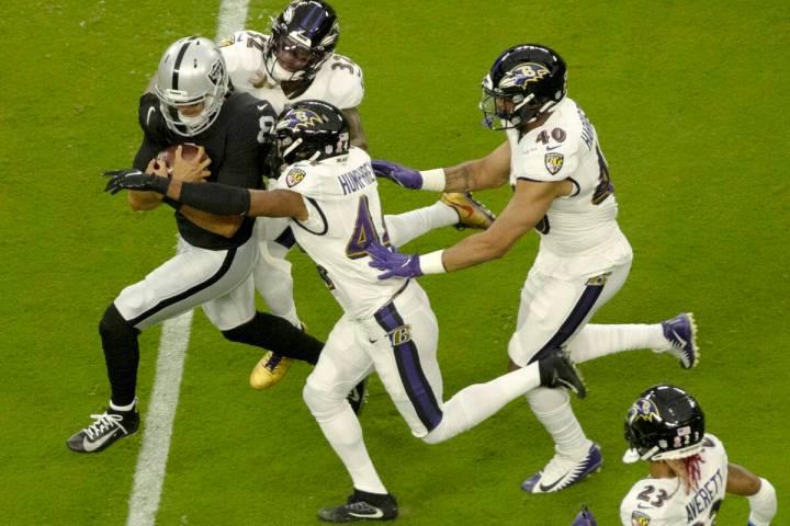 Raiders quarterback Marcus Mariota (8) rushes against the Ravens defense during an NFL football ...