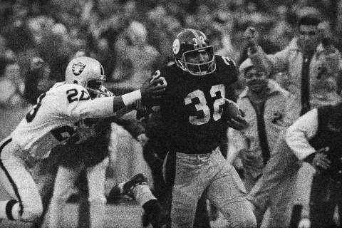 Franco Harris (32) of the Pittsburgh Steelers eludes a tackle by Jimmy Warren of the Oakland Ra ...