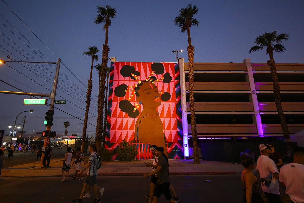 Attendees pass by a mural during the final day of the Life is Beautiful festival in downtown La ...