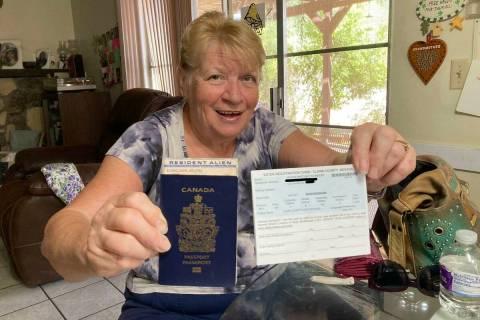 Helena Schneider holds up her Canadian passport, resident alien card and Nevada voter registrat ...