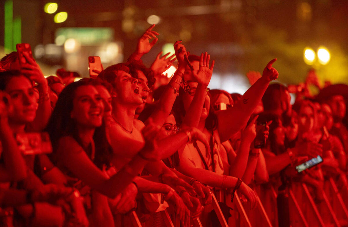 Fans bathed in red light cheer for Tame Impala performing on the Downtown Stage during day one ...