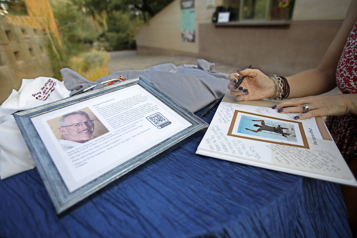 Kelly Slaughter of Las Vegas writes a message on a book when she arrives at a celebration of li ...