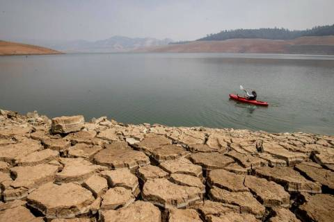 A kayaker fishes in Lake Oroville as water levels remain low due to continuing drought conditio ...