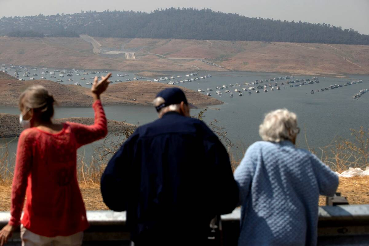 Visitors look out over Lake Oroville as water levels remain low due to continuing drought condi ...