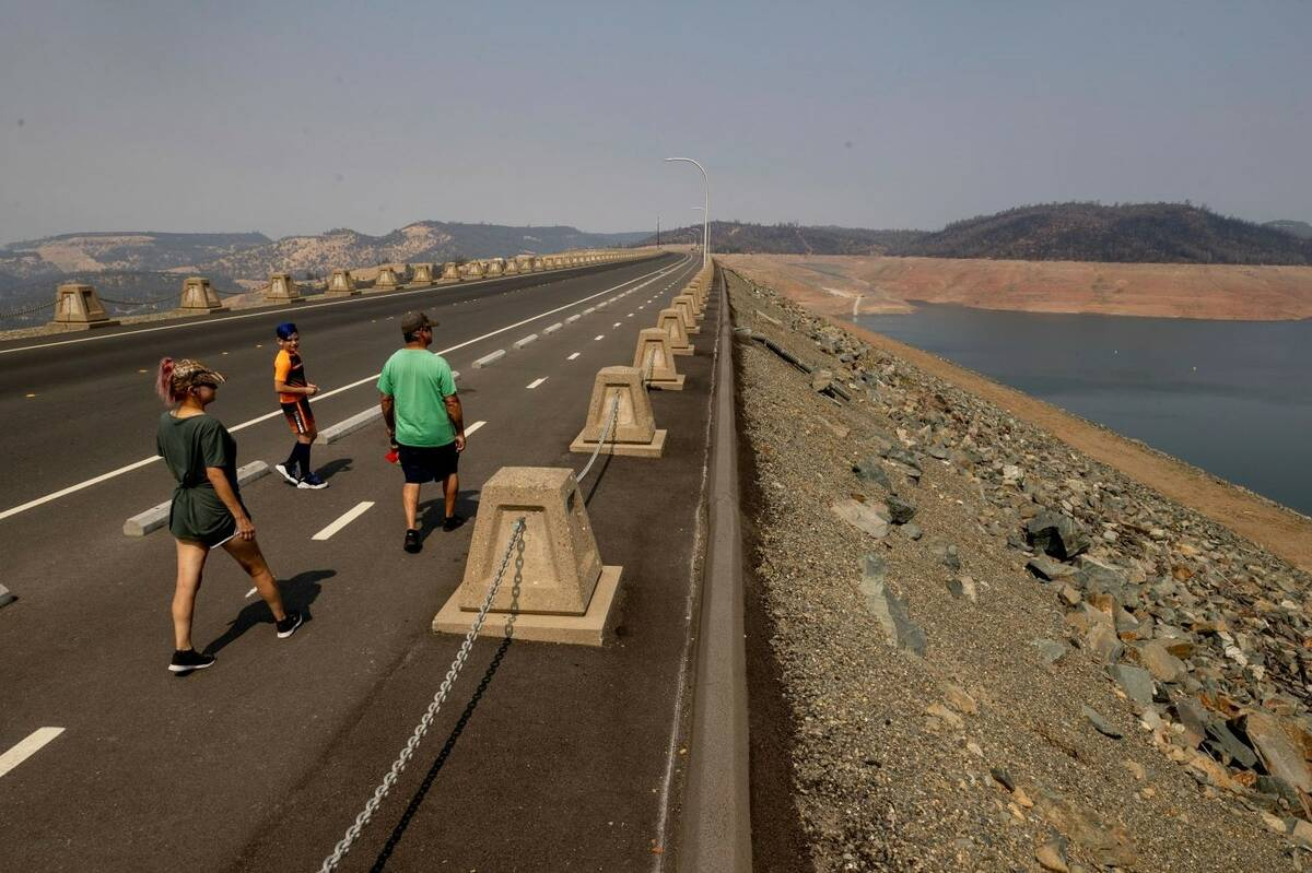 Pedestrians walk across Oroville Dam at Lake Oroville State Recreation Area as drought conditio ...