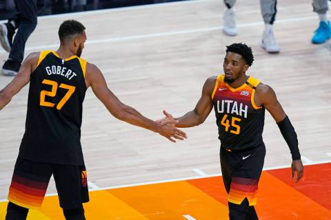 Utah Jazz's Rudy Gobert (27) congratulates Donovan Mitchell (45) after he scored against the Me ...