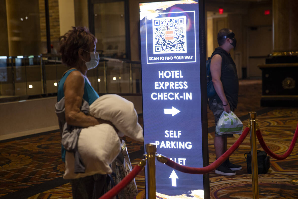 A sign directs guests to new machines that allow a self check-in at the Caesars Palace hotel-ca ...
