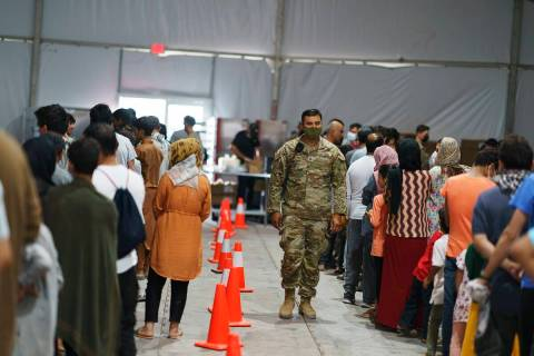 Afghan refugees line up for food in a dining hall at Fort Bliss' Doña Ana Village where th ...