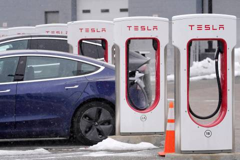A Tesla electric vehicle, left, sits in a charging station at a dealership, Thursday, Feb. 18, ...