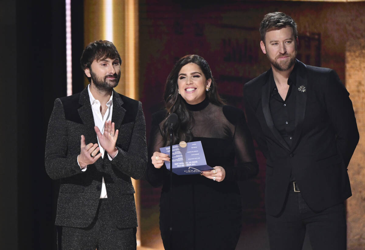 Dave Haywood, from left, Hillary Scott, and Charles Kelley of Lady Antebellum present the award ...