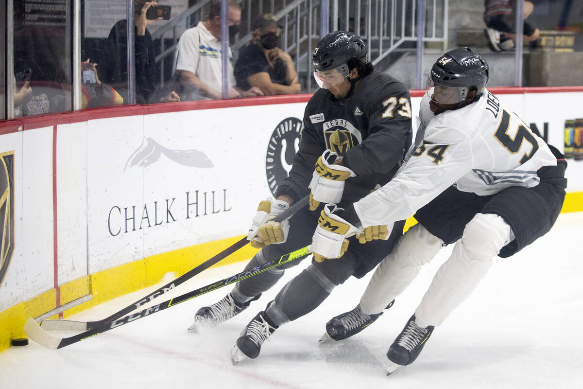 Golden Knights forward Gage Quinney (73) and forward Jermaine Loewen (54) compete for the puck ...