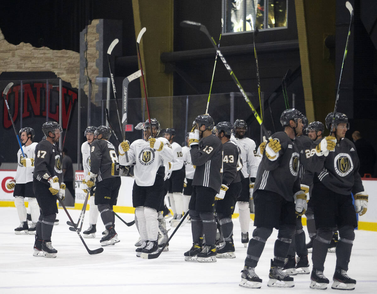 Golden Knights players throw up their sticks for the fans after an NHL hockey training camp scr ...