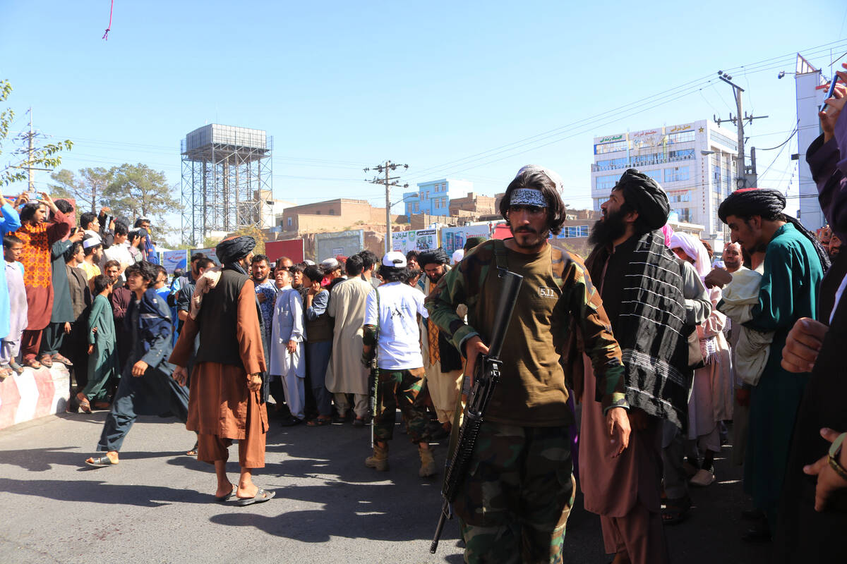 People gather in the main square of Herat city in western Afghanistan, where the Taliban hanged ...