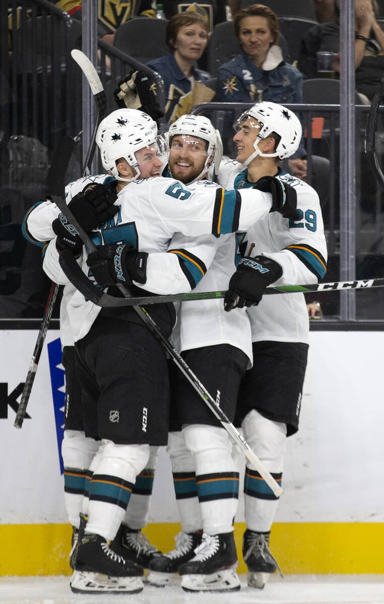 Sharks forward Adam Raska, left, is hugged by teammates left wing Jeffrey Viel, center, and def ...