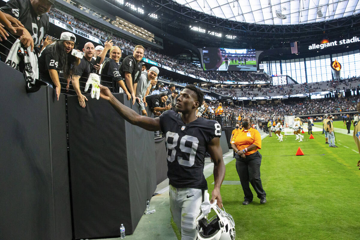 Raiders wide receiver Bryan Edwards (89) hands a glove to a fan while heading off the field aft ...