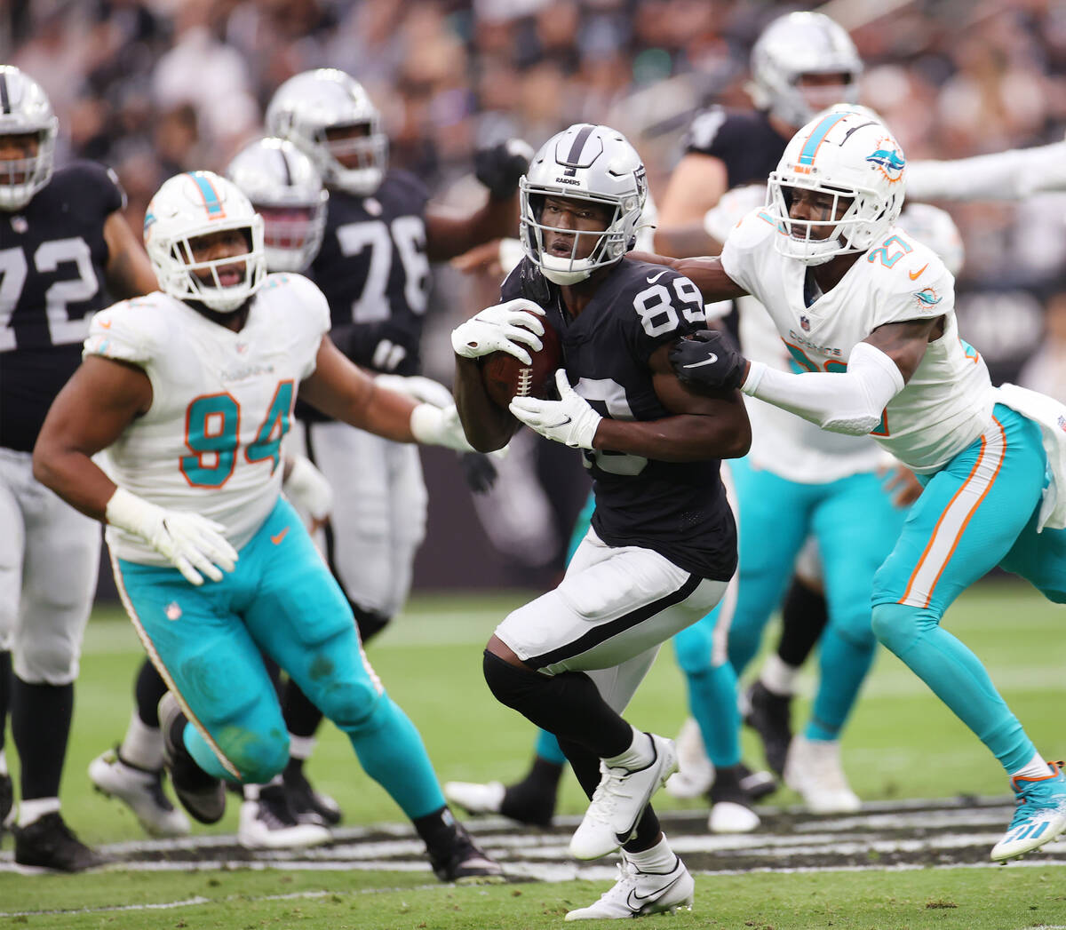 Las Vegas Raiders wide receiver Bryan Edwards (89) makes a catch as he gets tackled by Miami Do ...
