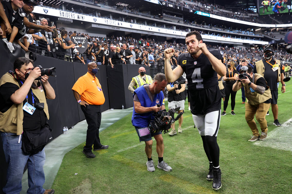 Las Vegas Raiders quarterback Derek Carr (4) raises his arms as he leaves the field after an ov ...