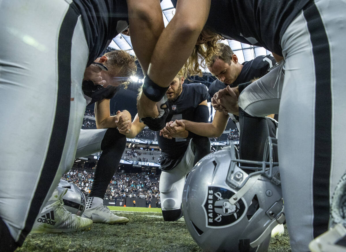 Raiders players pray together on the field after defeating the Miami Dolphins 31-28 in the over ...