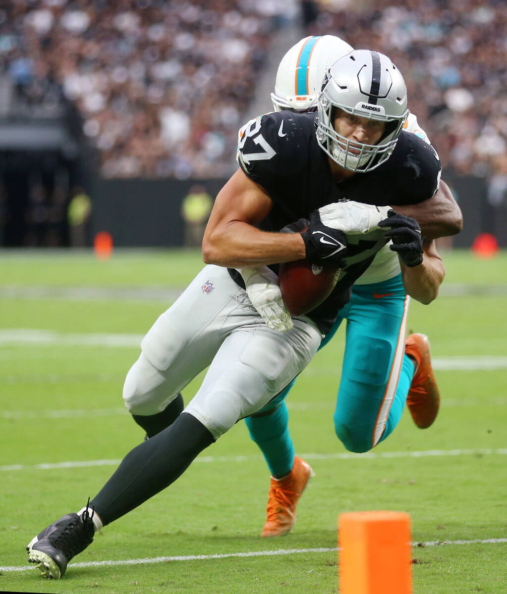 Las Vegas Raiders tight end Foster Moreau (87) is tackled by Miami Dolphins free safety Eric Ro ...