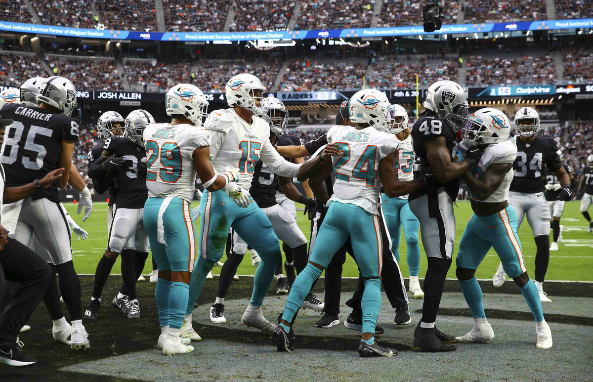 Referees try to break up the Miami Dolphins and Raiders during the first half of NFL game at Al ...