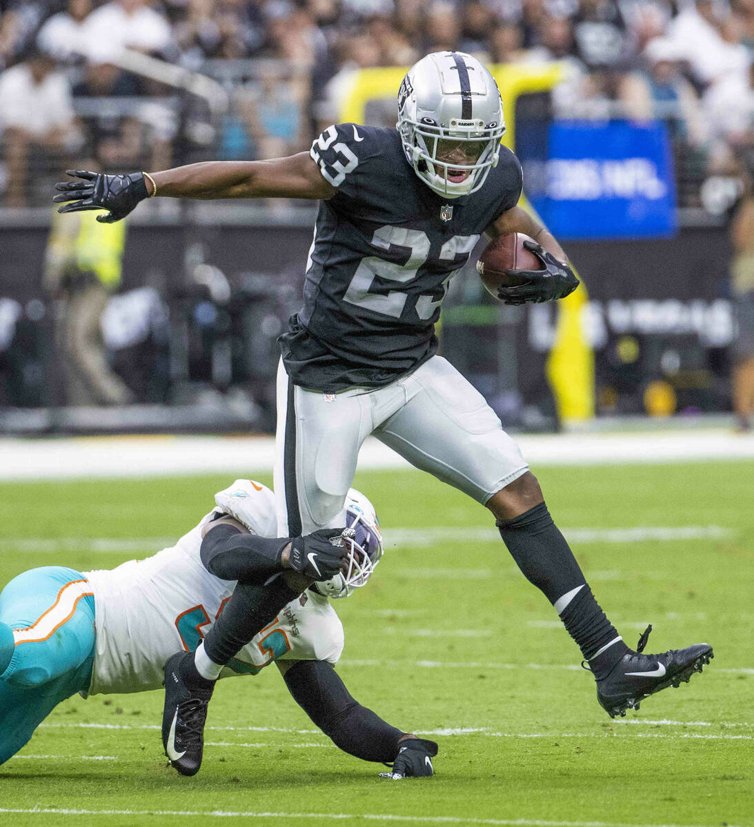 Las Vegas Raiders running back Kenyan Drake (23) looks to break a tackle by Miami Dolphins midd ...