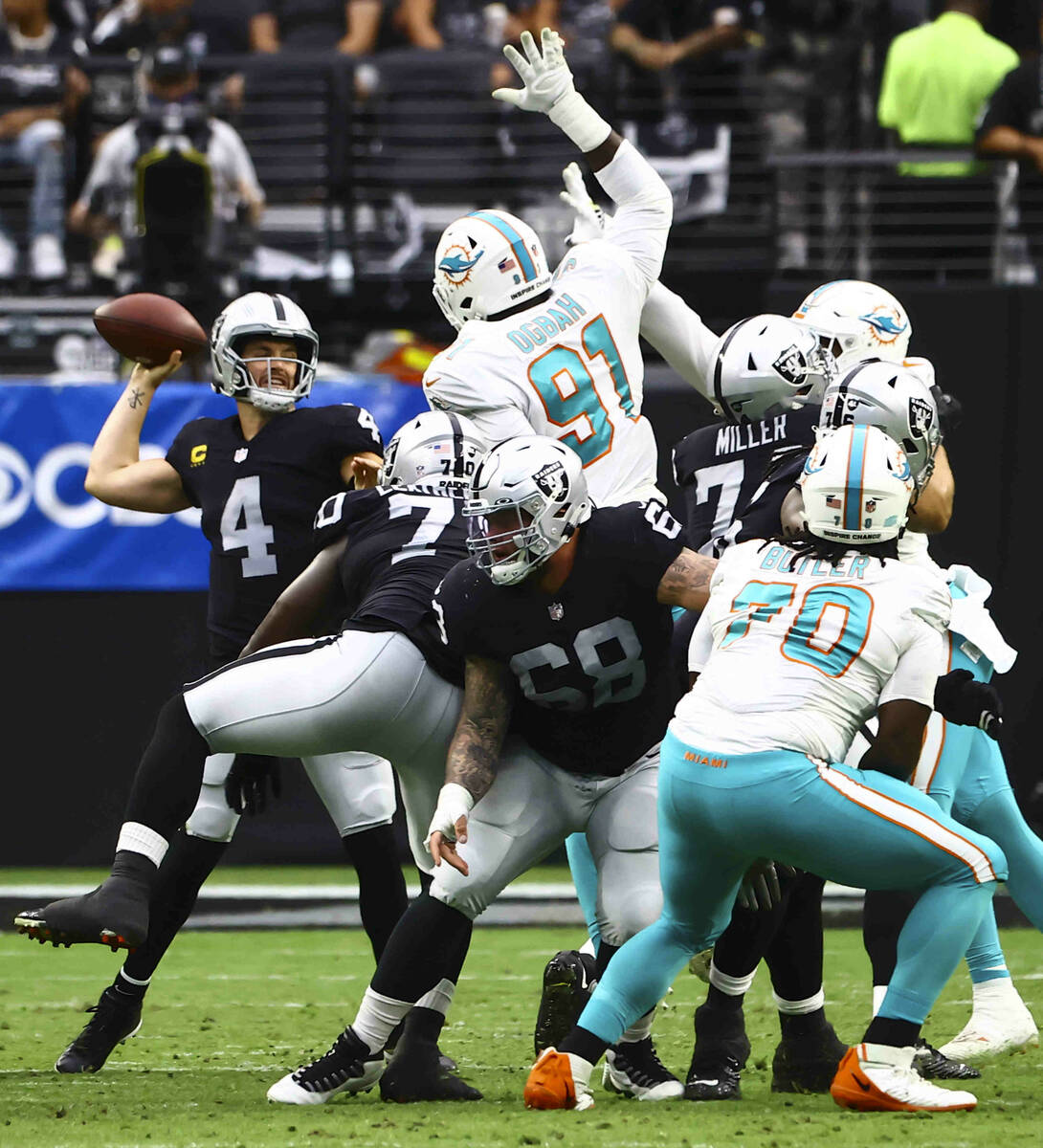 Raiders quarterback Derek Carr (4) looks to throw a pass under pressure from the Miami Dolphins ...