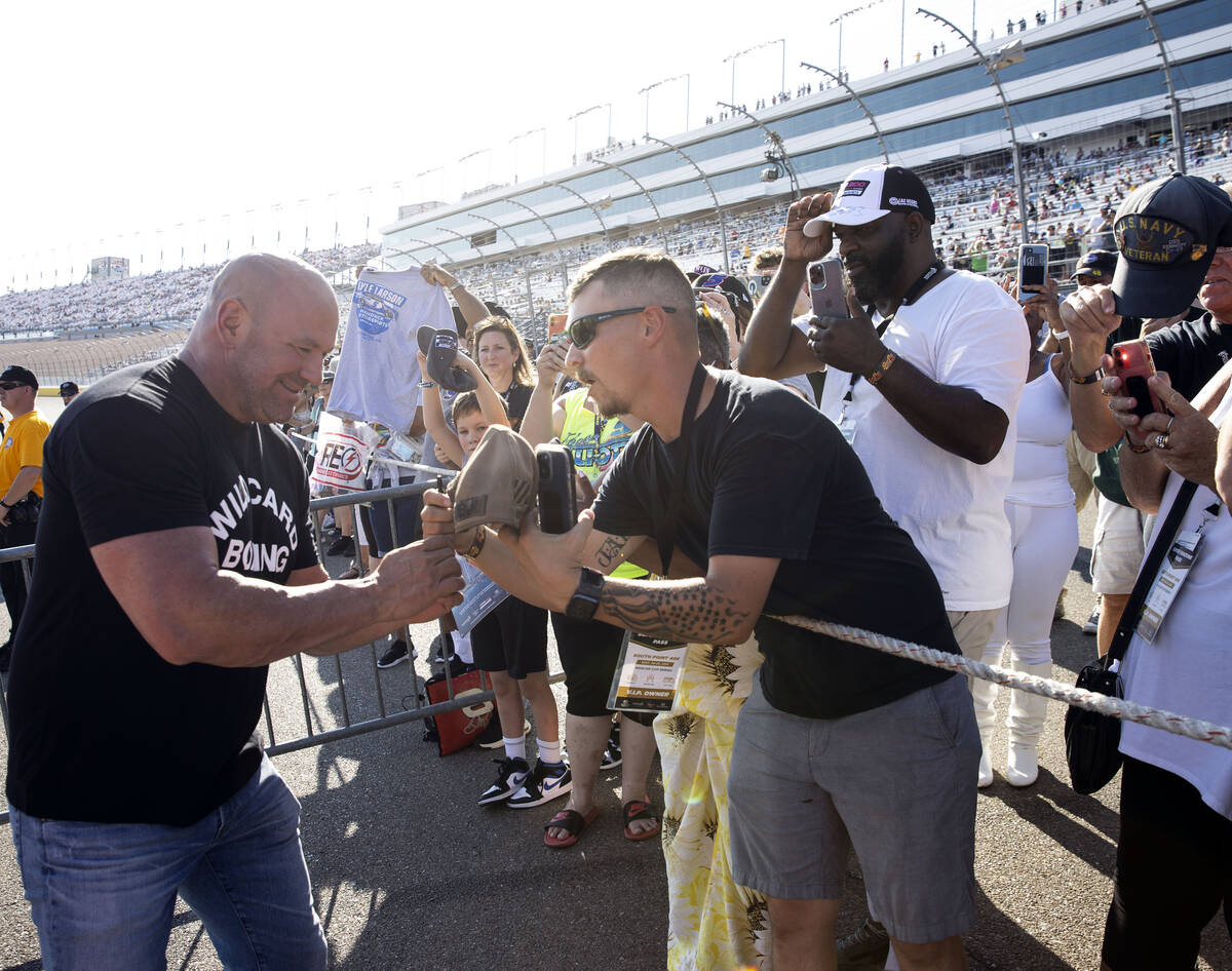 Dana White, left, president of the Ultimate Fighting Championship, signs autographs to fans dur ...