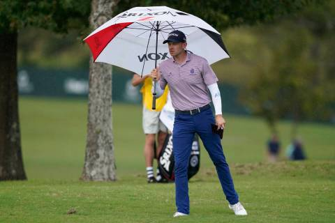 Jared Wolfe steps out with his umbrella as rain begins to fall during the first round of the Sa ...