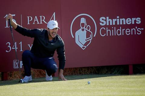 Brooks Koepka stretches while waiting to tee off on the 14th hole during the Shriners Children& ...