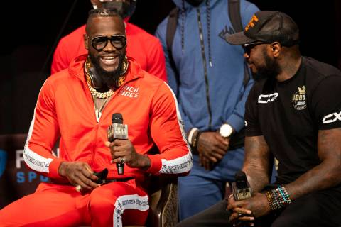 Deontay Wilder, left, speaks to his trainer, Malik Scott, during a news conference in advance o ...