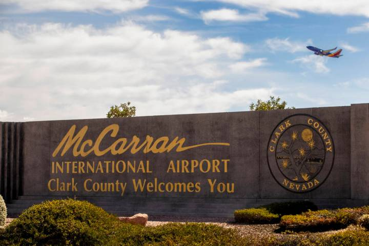 A sign for McCarran International Airport with a plane taking off above it at Tropicana Avenue ...