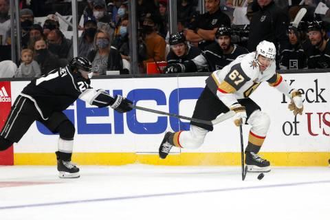 Los Angeles Kings forward Vladimir Tkachev (21) tries to slow Vegas Golden Knights forward Max ...