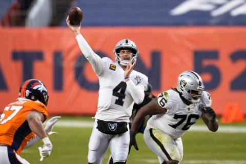 Raiders quarterback Derek Carr (4) gets a pass away with pressure from Denver Broncos defensive ...