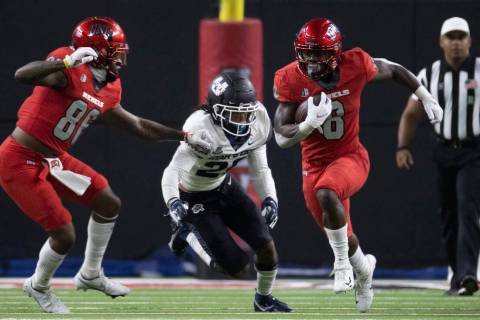 Rebels running back Charles Williams (8) sprints up field past Utah State Aggies safety Monte' ...