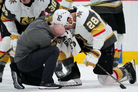 Vegas Golden Knights left wing William Carrier (28) is looked at by a trainer after taking a sk ...