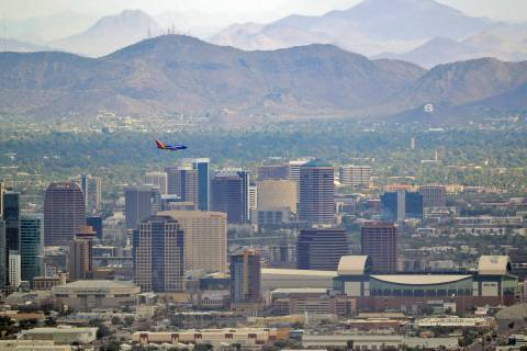 In this Tuesday, July 24, 2018 photo, a jet comes in for approach over downtown Phoenix. (AP Ph ...