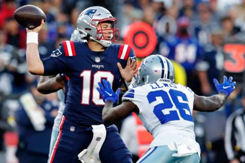 New England Patriots quarterback Mac Jones (10) throws while pressured by Dallas Cowboys corner ...