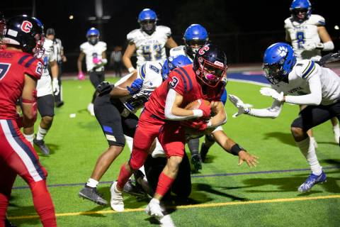Coronado's Chris Avila carries the ball out of bounds as several Sierra Vista players close in ...