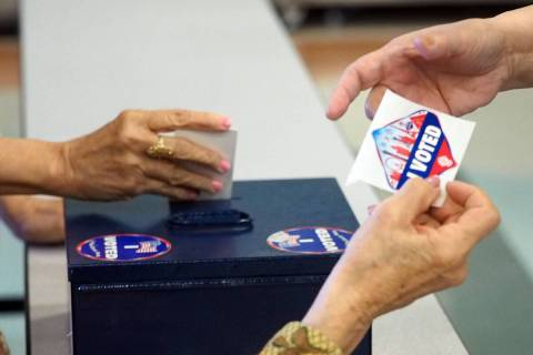 A poll worker hands a voter a sticker showing that she has voted as another poll worker drops t ...